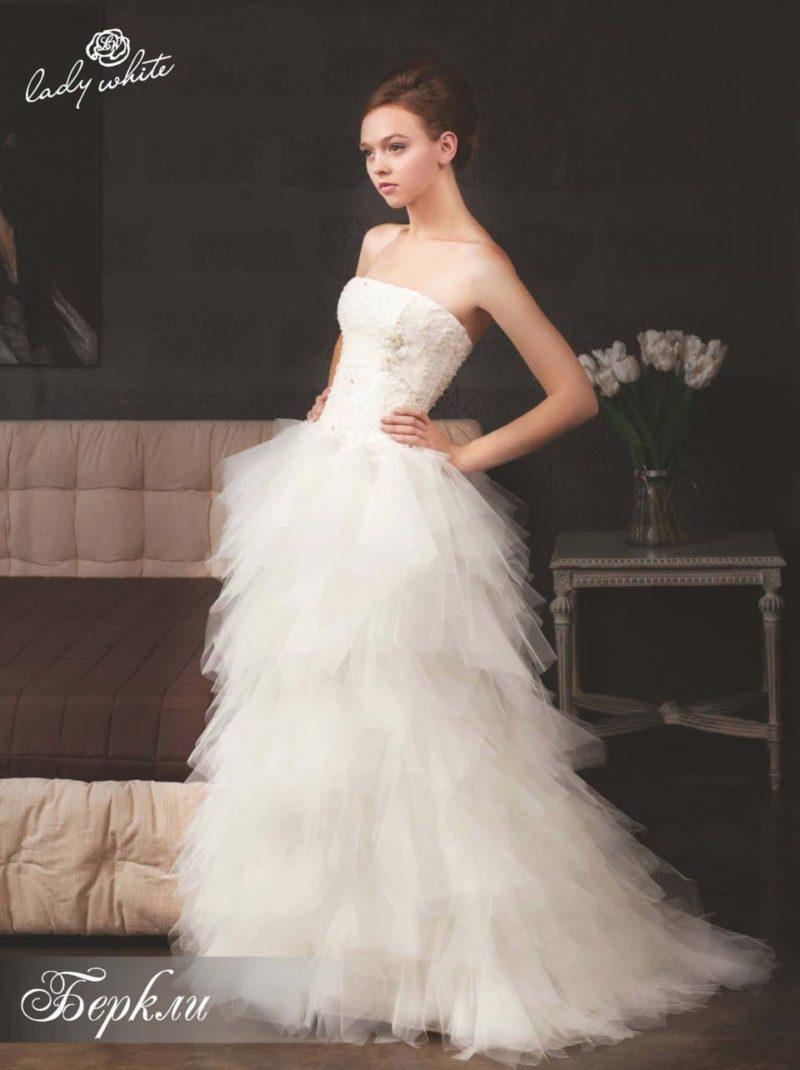 Открытое свадебное платье с пышной отделкой юбки.