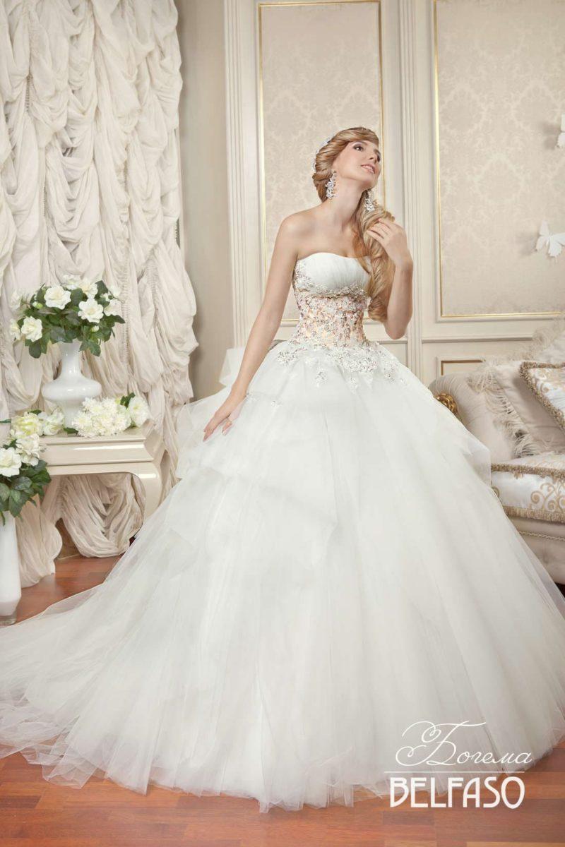 Пышное свадебное платье с открытым корсетом, украшенным кружевом, и многоярусной юбкой.