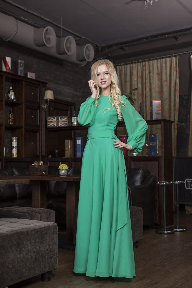 Закрытое вечернее платье с широким длинным рукавом и прямой юбкой.