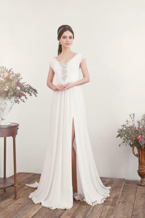 Прямое свадебное платье с разрезом на юбке и серебристой вышивкой.