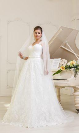 Лаконичное свадебное платье «принцесса» с широким атласным поясом и кружевным декором юбки.