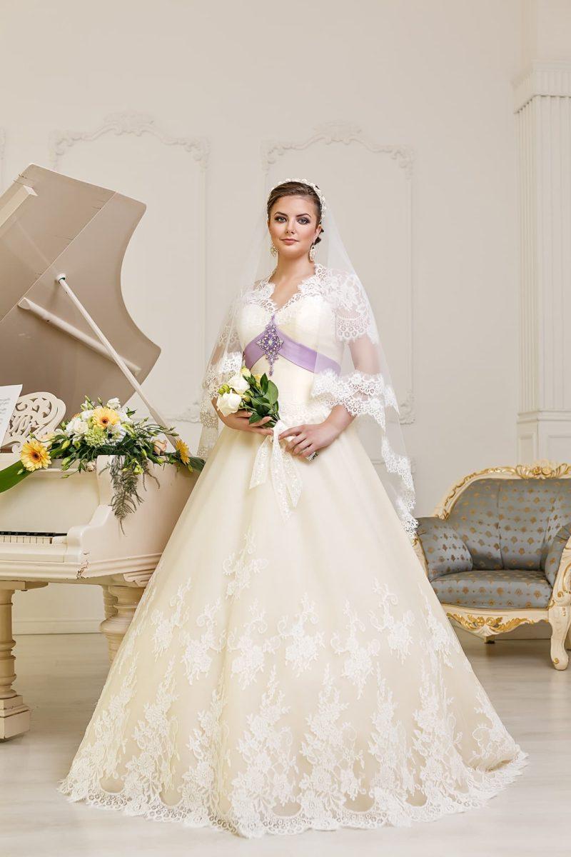 Кремовое свадебное платье пышного кроя с кружевным декором подола и лиловым поясом.