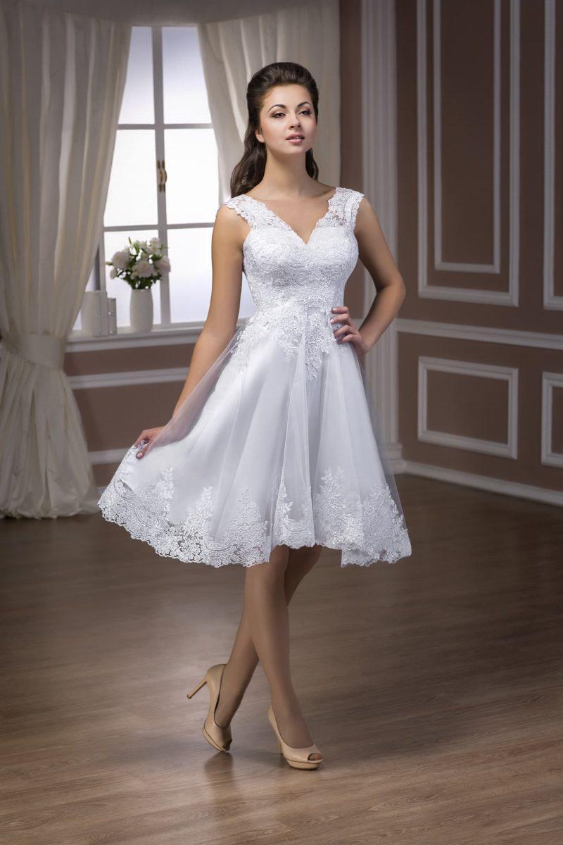 Свадебное платье длиной выше колена, украшенное плотными кружевными аппликациями.