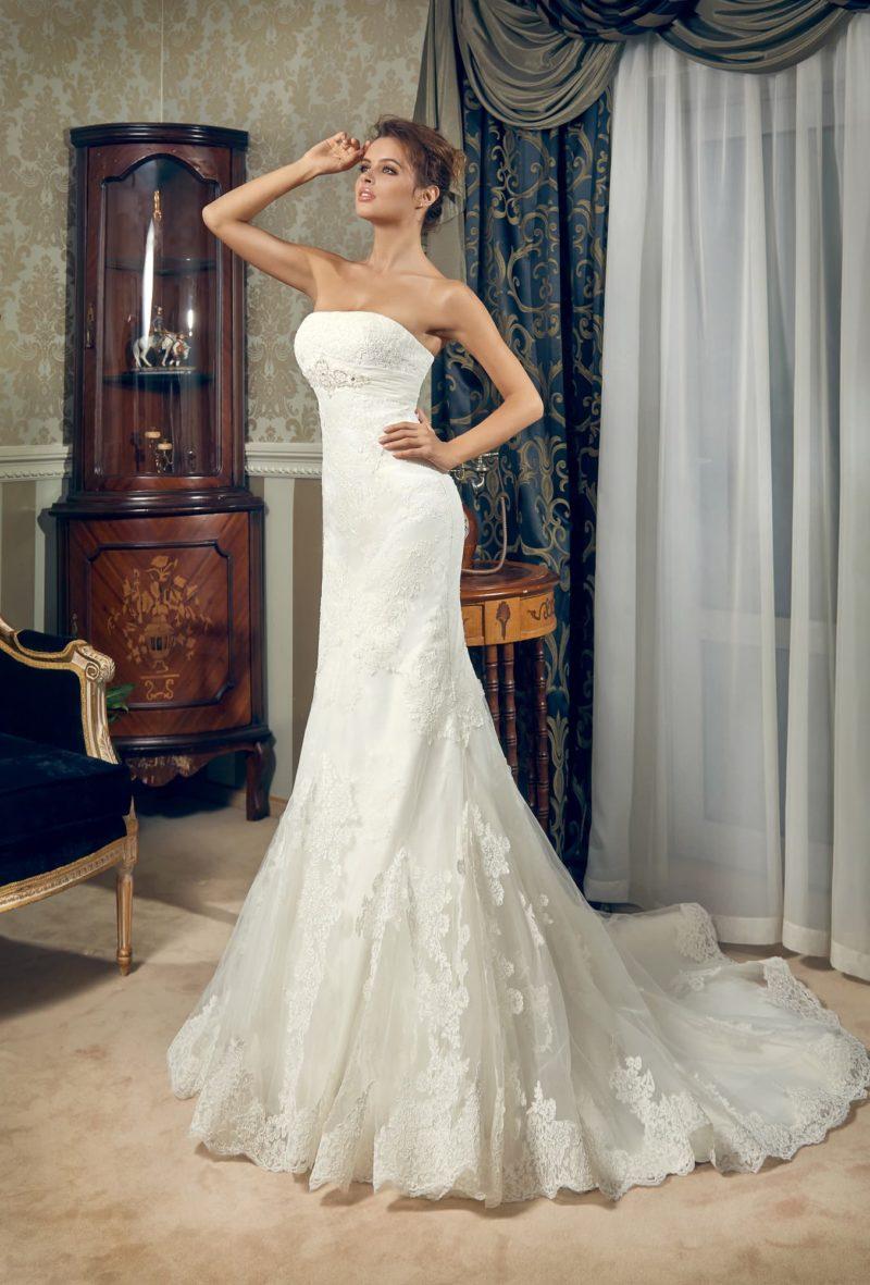 Открытое свадебное платье с прямым декольте и многослойной юбкой с кружевным декором.