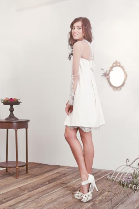 Свадебное платье с кружевной юбкой до середины бедра и облегающим рукавом.
