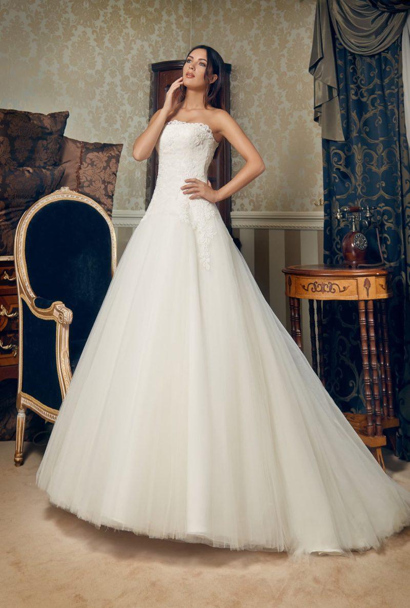 Роскошное свадебное платье с открытым кружевным лифом и многослойной юбкой.