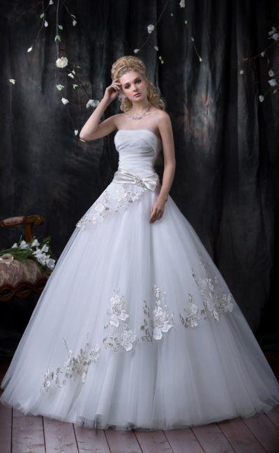Эксцентричное свадебное платье с пышной юбкой, покрытой аппликациями, и атласным поясом.