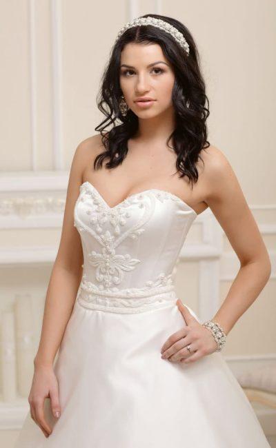 Атласное свадебное платье с открытым лифом в форме сердца и фактурной отделкой корсета.