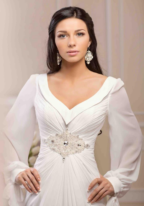 Драматичное свадебное платье с глубоким декольте и широкими полупрозрачными рукавами.