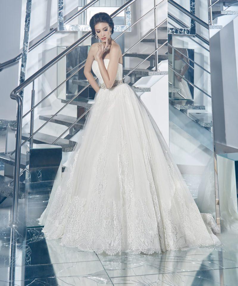 Нежное свадебное платье с открытым лифом, сияющим широким поясом и кружевом по низу подола.