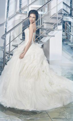 Чарующее свадебное платье с открытым лифом прямого кроя и многослойной юбкой с оборками.