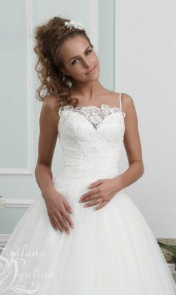 Пышное свадебное платье с узкими бретелями и кружевной отделкой.