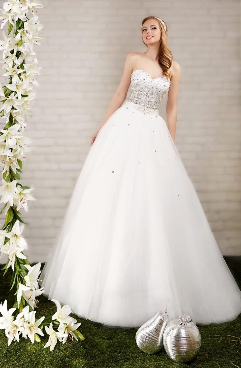 Пышное свадебное платье с открытым лифом в форме сердца, украшенным бисерной отделкой.
