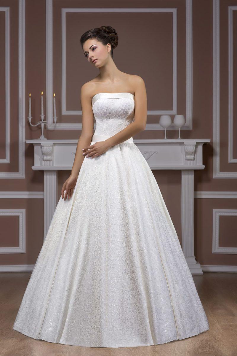 Свадебное платье пышного кроя с атласным поясом и лаконичным открытым корсетом.