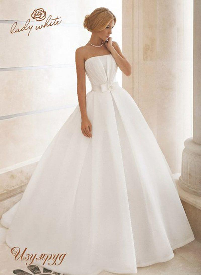 Пышное свадебное платье с прямой линией декольте и шлейфом сзади.