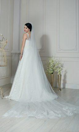 Свадебное платье пышного кроя, покрытое глянцевым кружевом, с фигурным вырезом под горло.