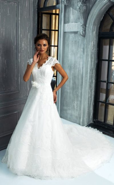 Изысканное свадебное платье с V-образным декольте и кружевной юбкой с небольшим шлейфом.
