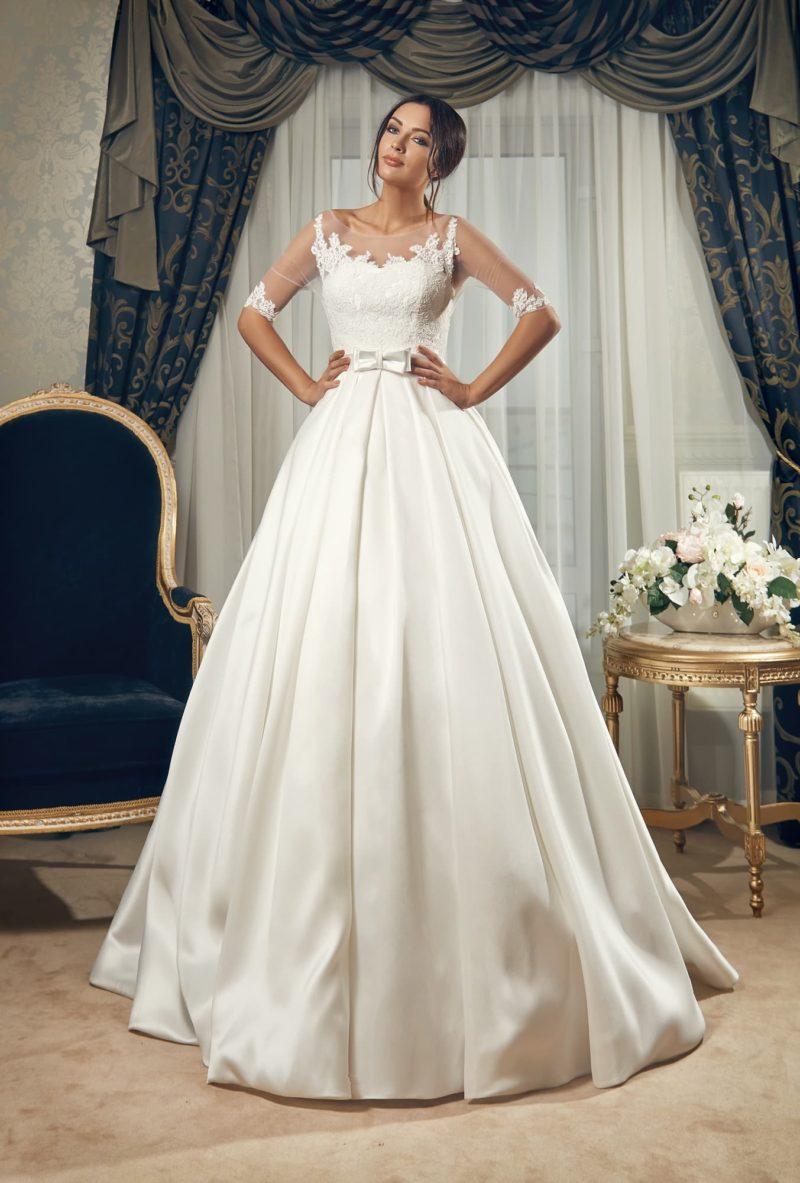 Атласное свадебное платье пышного кроя с длинными полупрозрачными рукавами и открытой спиной.