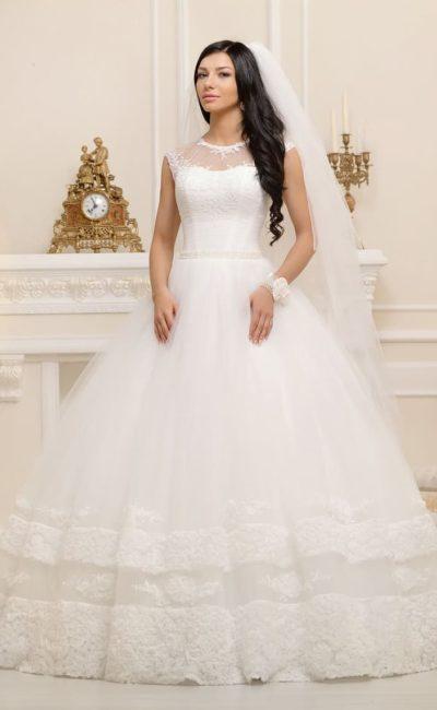 Закрытое свадебное платье с округлым вырезом и многослойной юбкой с декором по низу подола.
