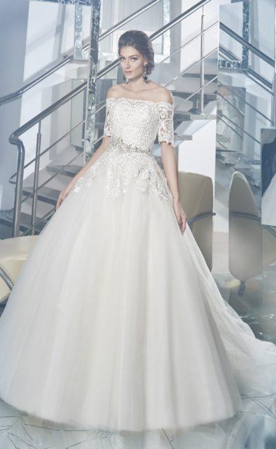 Пышное свадебное платье с фактурным верхом, украшенным кружевом, и сияющим поясом.