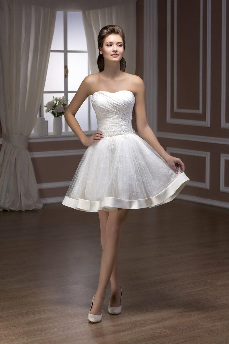 Кокетливое свадебное платье пышного силуэта с юбкой выше колена, украшенное кружевом и атласом.