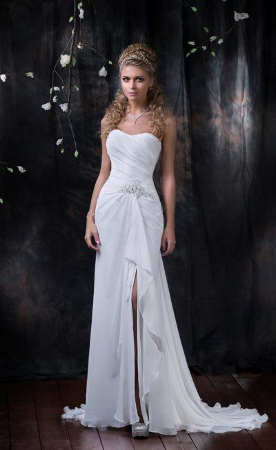 Прямое свадебное платье с деликатным открытым корсетом и разрезом на юбке со шлейфом.