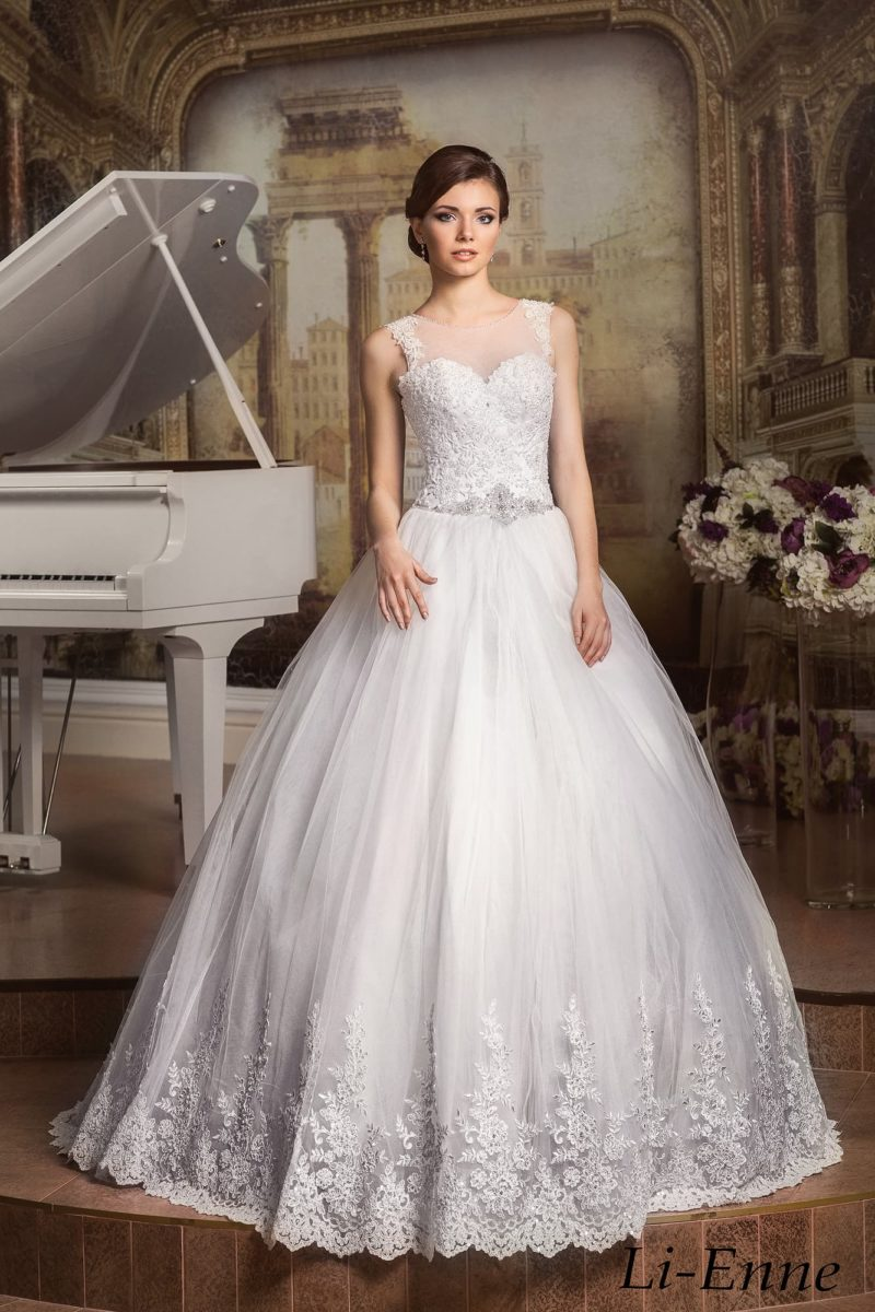 Торжественное свадебное платье с многослойным подолом, украшенным кружевными аппликациями.