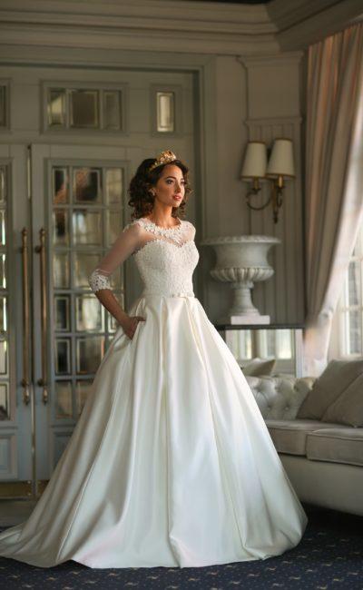 Потрясающее свадебное платье с пышной атласной юбкой и длинными кружевными рукавами.