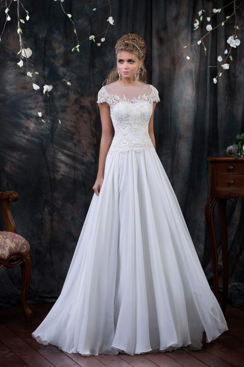 Нежное свадебное платье с кружевным корсетом с коротким рукавом и юбкой, украшенной складками.