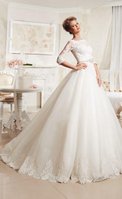 Пышное свадебное платье с элегантным верхом с длинным рукавом, оформленным кружевом.