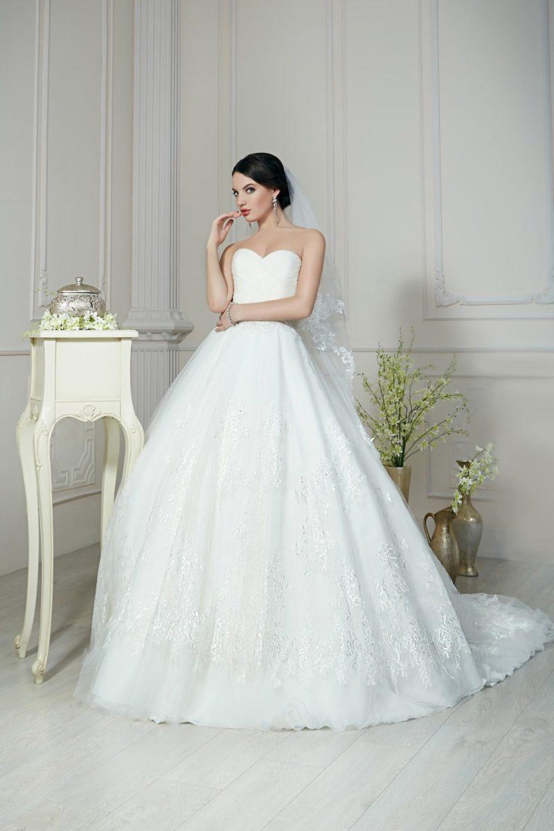 Свадебное платье с открытым лифом-сердечком и пышной юбкой, покрытой аппликациями.