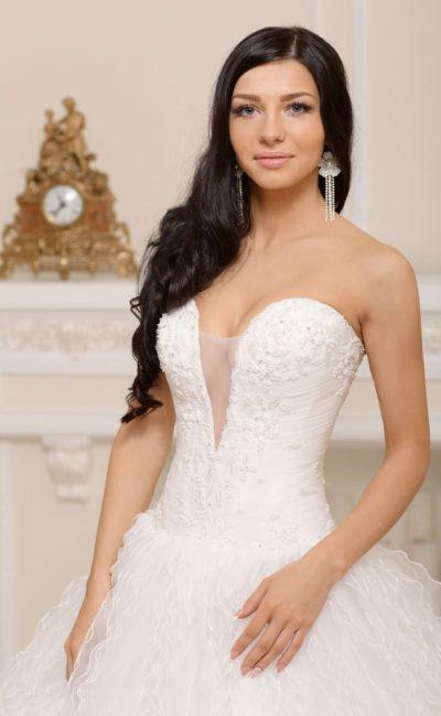 Пышное свадебное платье с полупрозрачным подолом и глубоким V-образным вырезом с тонкой вставкой.