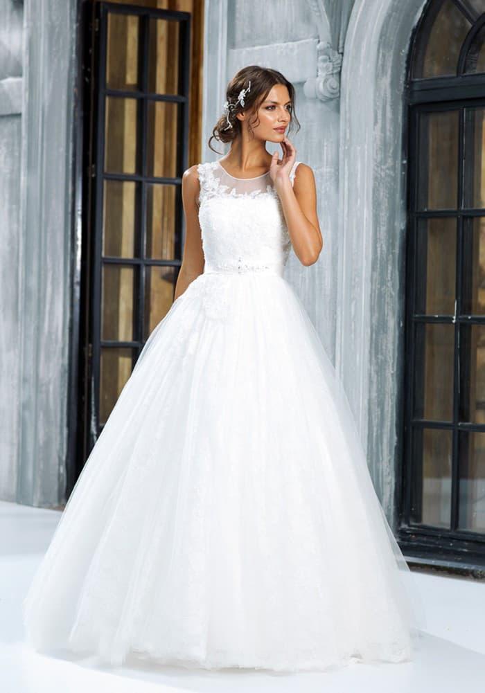 Пышное свадебное платье с округлым вырезом, изящно оформленным полупрозрачной тканью.