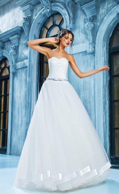 Элегантное свадебное платье с кружевным лифом в форме сердца и пышной юбкой, украшенной по низу подола атласом.