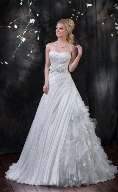 Стильное свадебное платье с открытым лифом с драпировками и пышной юбкой с объемным декором.