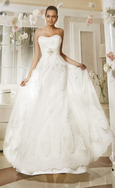 Открытое свадебное платье с прозрачным верхом юбки и широким поясом на талии.