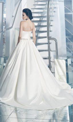 Атласное свадебное платье с сияющим поясом на талии и выразительной юбкой со шлейфом.