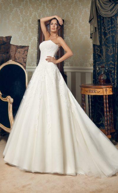 Изысканное свадебное платье с лаконичным открытым лифом и многослойной юбкой.