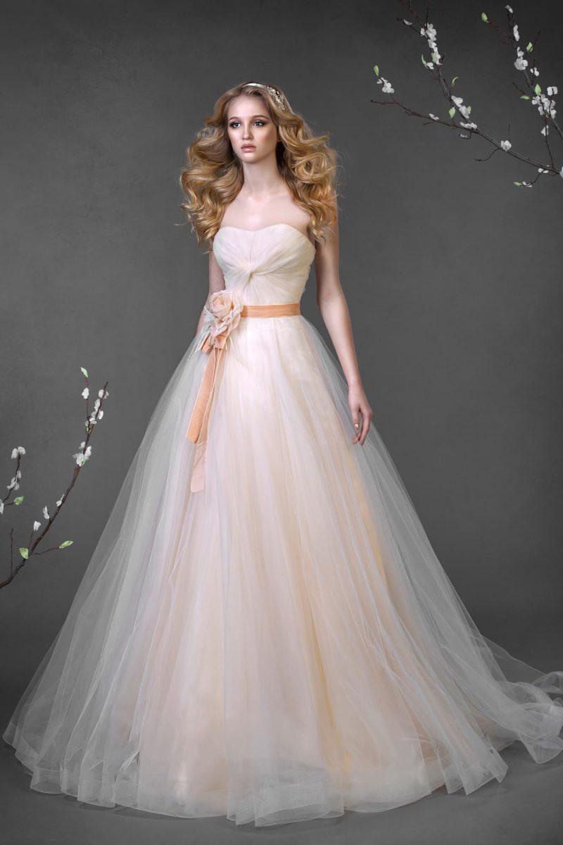 Кремовое свадебное платье с пышным силуэтом и широким атласным поясом на линии талии.