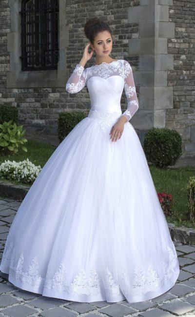 Выразительное свадебное платье пышного кроя с кружевным декором низа подола и длинными рукавами.