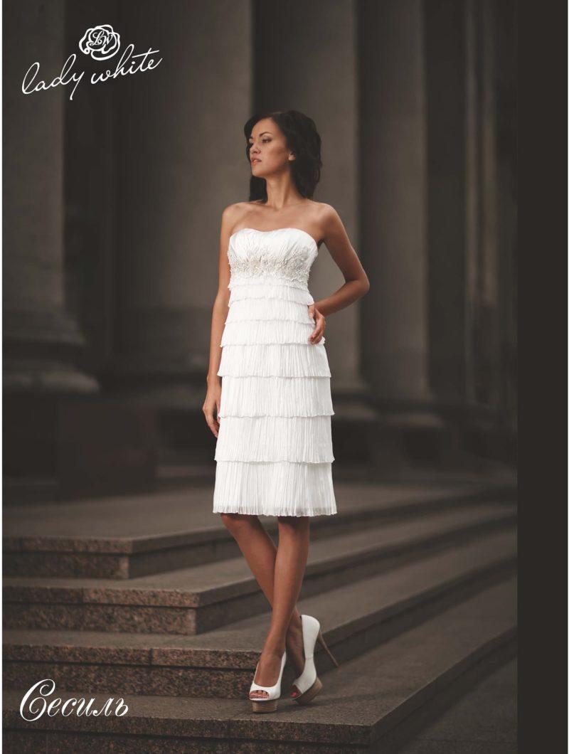 Прямое свадебное платье с оборками на юбке до колена.