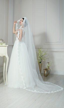 Пышное свадебное платье с закрытым кружевным лифом и вырезом «замочная скважина» сзади.