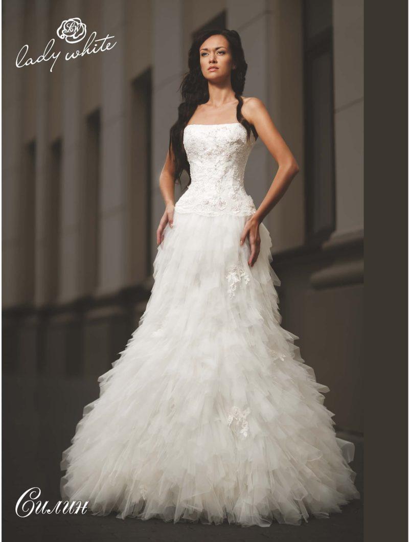 Очаровательное свадебное платье с открытым лифом и объемной отделкой юбки.