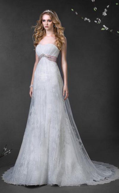 Романтичное свадебное платье с кружевным полупрозрачным верхом юбки и розовым поясом из атласа.