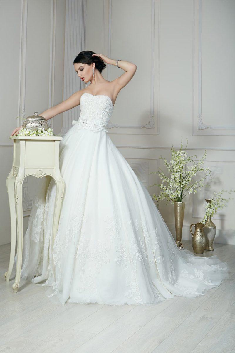 Сдержанное свадебное платье с воздушной юбкой и фактурным открытым корсетом с бутоном на талии.