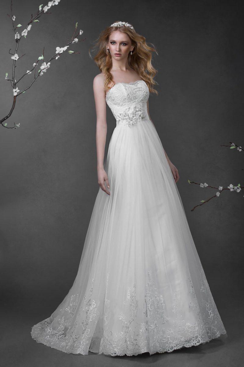Нежное свадебное платье с кружевным корсетом, романтичным поясом и многослойной юбкой.