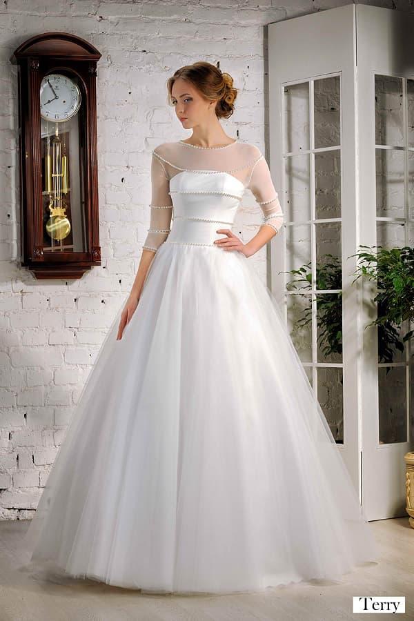 Пышное свадебное платье с атласным корсетом и полупрозрачными длинными рукавами.