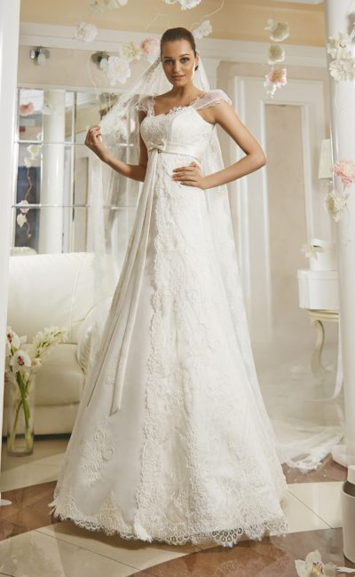 Романтичное свадебное платье с завышенной линией талии и кружевной отделкой по всей длине.