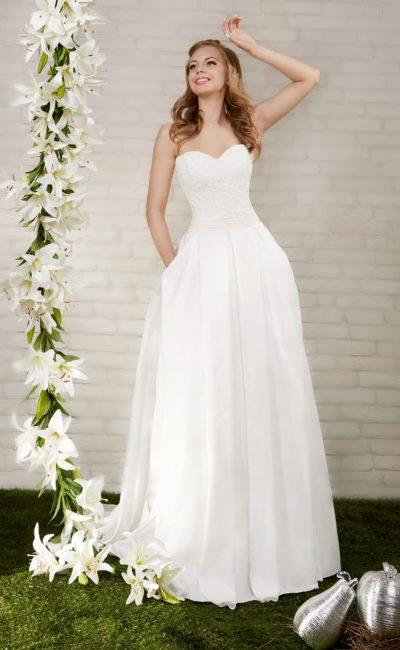 Утонченное свадебное платье с открытым лифом, покрытым кружевом, и широким поясом на талии.