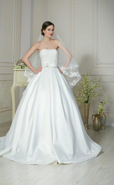 Пышное свадебное платье с роскошной атласной юбкой, бантом на талии и кружевным корсетом.